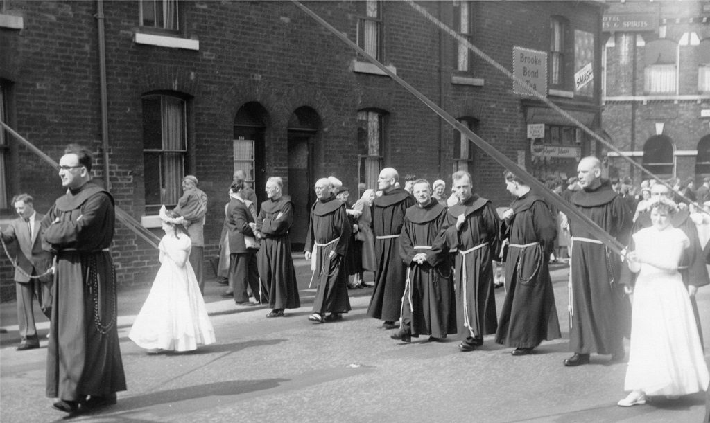 Manchester Monastery Whit walk around 1960. The friars walk behind the banner with the girls holding the banner strings.